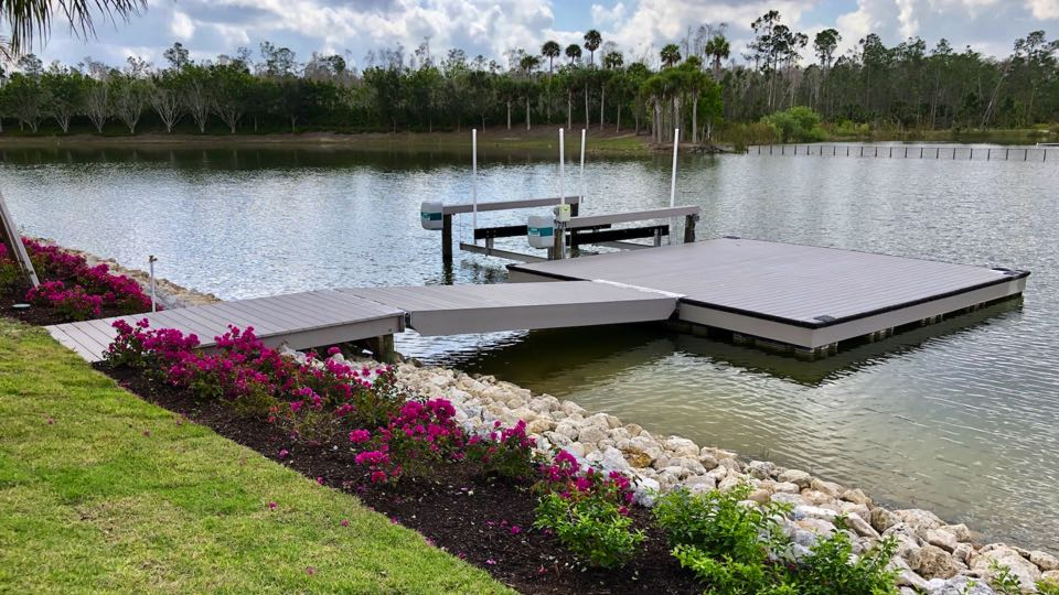 20' x 20' custom designed and built floating dock with Quality Boat Lift featuring Azek vinyl decking, black fold down boat cleats and rubber bumpers. Miromar Lakes